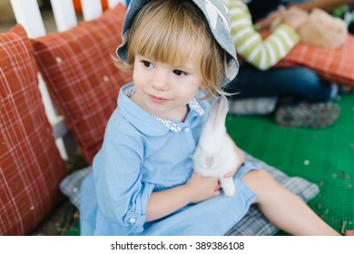 Cute little girl sitting on the pillow and holding a little white rabbit in her hands outdoors