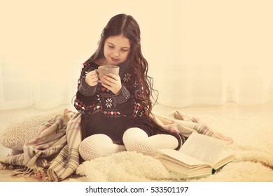Cute little girl sitting on floor with cup of coffee
