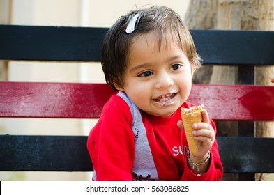 A Cute Little Girl Sitting On A Bench And Eating An Ice-Cream Cone