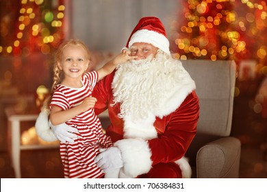 Cute little girl sitting on Santa's lap in room with beautiful Christmas decorations