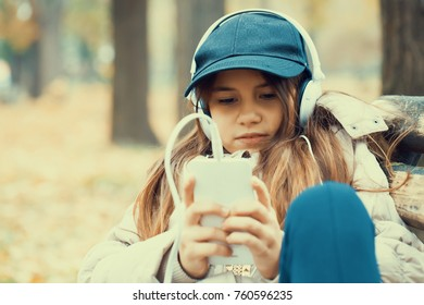 Cute little girl sitting on a park bench, listening to music on headphones and using a mobile phone. High ISO
