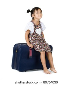 cute little girl sitting on her suitcase, isolated on white background