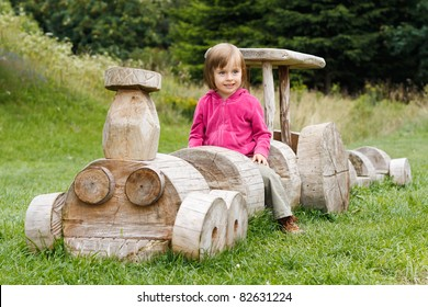Cute little girl sitting on a wooden train