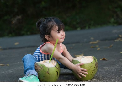 Cute little girl sitting at the pavement holding a fresh coconut. Outdoor summer picture.
