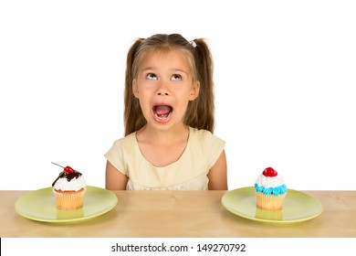 A cute little girl is sitting at the table with two delicious cupcakes in front of her, making funny expression on her face, isolated
