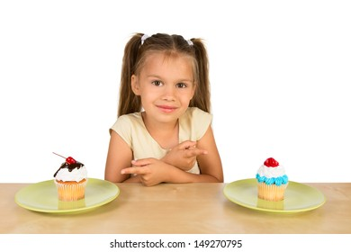 A cute little girl is sitting at the table  with two delicious cupcakes in from of her, pointing at them with crossed hands, isolated