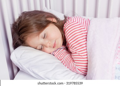 cute little girl sleeping in her bed