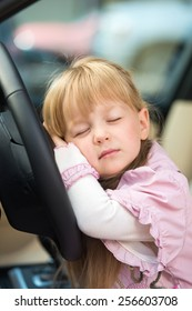 Cute little girl sleeping on the steering wheel of the car