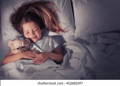 Cute little girl sleeping with teddy bear in bed