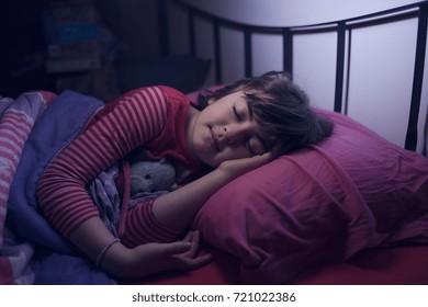 Cute little girl sleeping with a teddy bear in her bedroom
