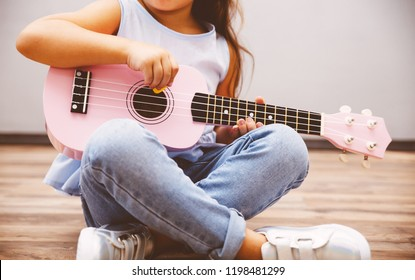 Cute little girl in smart fashiony clothes playing pink ukulele sitting on floor
