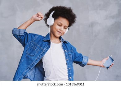 Cute little girl with smartphone and headphones listening to music and dancing