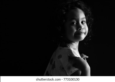 Cute little girl smiling in black and white format.