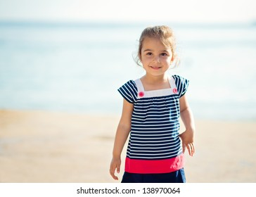 Cute Little Girl Smiling by the Ocean