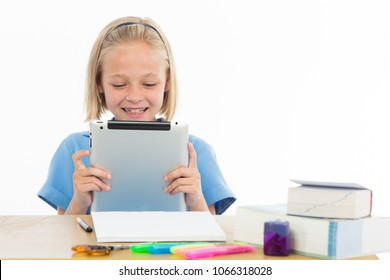 Cute little girl smiling at her tablet infront of her school books.