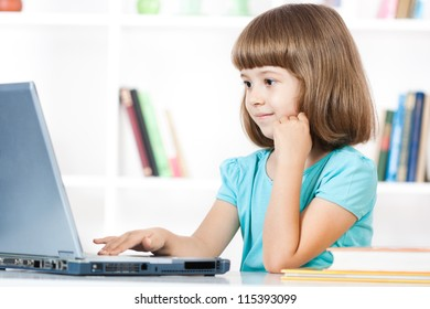 Cute little girl smiling and looking at laptop ,Little girl using laptop