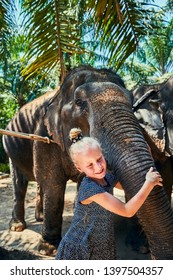 Cute little girl smiling while hugging the trunk of an Asian elephant at an animal sanctuary in Thailand