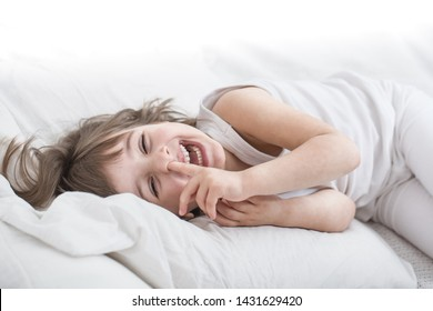 Cute little girl smiling while lying in a cozy white bed with , the concept of children's rest and sleep