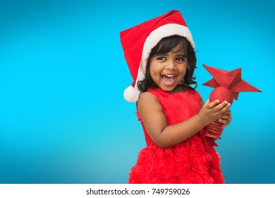 Cute little girl smiling while playing with Xmas decorated items