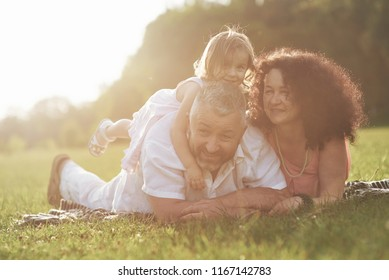 A cute little girl is spending time with her beloved grandfather and grandmather in the park. They had a picnic on the grass.
