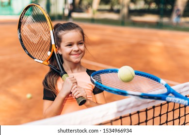 Cute little girl in sportswear with a racket in her hands on the tennis court
