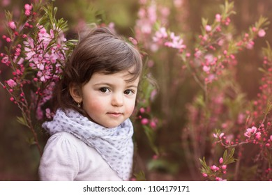 cute little girl in spring blooms and flowers