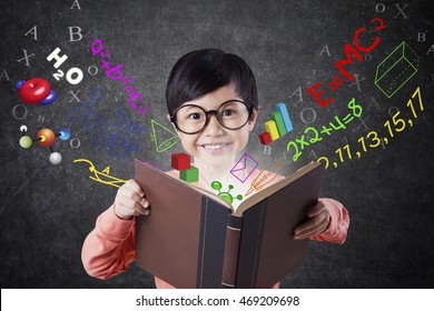 Cute little girl standing in the classroom while reading a book with formula of math, science, and physics