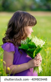 Cute little girl standing in a field and smiling. Portrait, joy, smile, dandelions, lily of the valley.