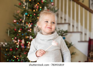 Cute little girl standing in front of a Christmas tree