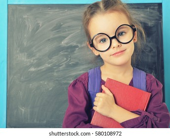 Cute little girl standing near blackboard in funny big glasses and holding book and smiling. Beautiful schoolgirl. Smart pupil girl in classroom.