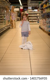 cute little girl is standing on  the  middle of a supermaket lane,her jacket is on the floor at her feet