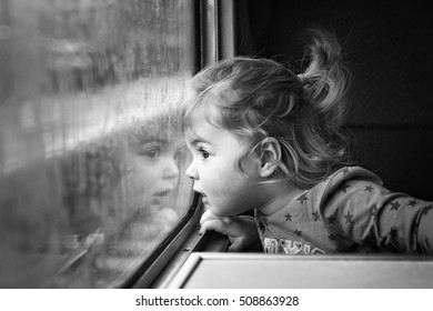 Cute little girl staring through window on a train journey