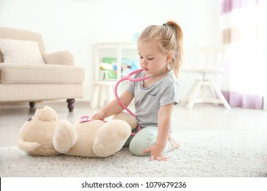 Cute little girl with stethoscope and toy bear playing at home