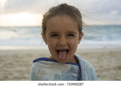 Cute little girl sticking out tongue / Girl at the beach covered with towel