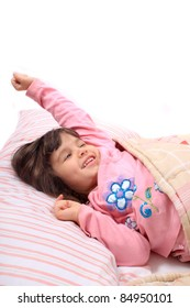 Cute little girl stretching her arms happily with a smile from waking up in her bed.