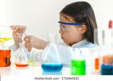 Cute little girl student child learning research and doing a chemical experiment while making analyzing and mixing liquid in glass at science class on the table.Education and science concept