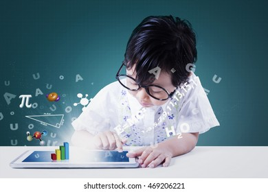 Cute little girl studying with a digital tablet and formula of math on the screen