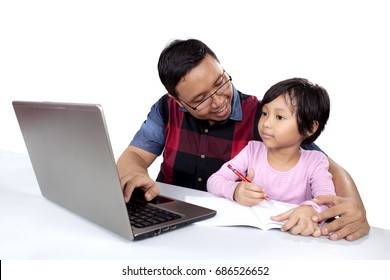 Cute little girl studying with her father while using a laptop and book on the table, isolated on white background