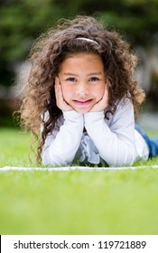 Cute little girl studying outdoors looking very happy