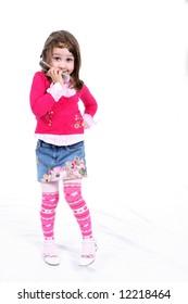 Cute little girl in stylish pink clothing, hand on her hip, holding her cell phone and grinning.