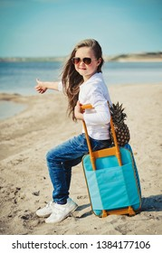Cute little girl with suitecase on the beach. Summertime concept.