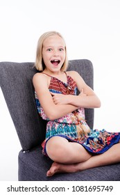 Cute little girl with a surprised look on her face while sitting on a chair in the studio.