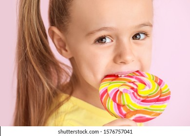 Cute little girl with sweet lollipop on color background