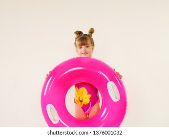 Cute little girl in swimsuit holding pink swimming circle. Isolated on background. Summer holidays.
