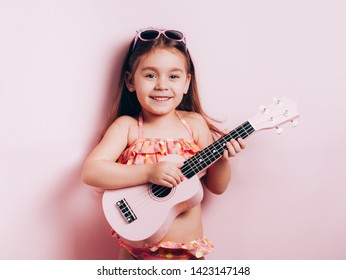 Cute little girl in swimsuit playing ukulele. Happy vacation concept.