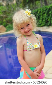 Cute little girl in a swimsuit at the pool