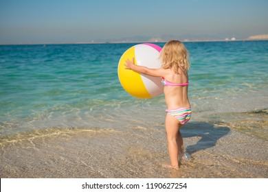Cute little girl in a swimsuit standing on the seashore with a big colorful ball in her hands. Summer vacation, travel and tourism.