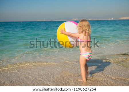 f50e4b75e2 Cute little girl in a swimsuit standing on the seashore with a big colorful  ball in