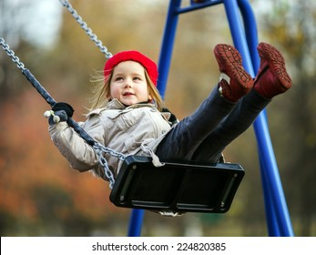 Cute little girl swinging on seesaw on children playground