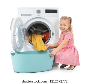 Cute little girl taking laundry out of washing machine on white background